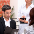 A man and a woman ordering at the restaurant, a waitress is writing the ord — Stock Photo #7376535