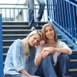 Two girlfriends sitting on the stairs at school - Stock Photo