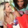 Excited girls watching their shopping bags - Stok fotoğraf
