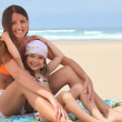 Mother and daughter sitting on a beach — Stock Photo #7377200