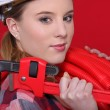 Tradeswoman holding corrugated tubing and a pipe wrench — Stock Photo #7377994