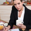 Young businesswoman eating her breakfast and looking at her agenda — Stock Photo #7378598