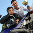 Stock Photo: Father and son holding a trophy