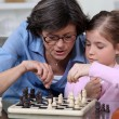 Mother teaching her daughter how to play chess. — Stock Photo #7378657