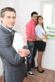 Young couple viewing a property with an agent — Stock Photo