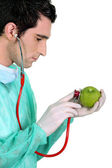 Doctor examining an apple with a stethoscope — Stock Photo