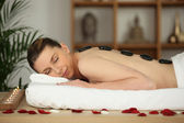 Laid woman having hot stones massage — Stock Photo
