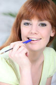 Portrait of a woman with a pen in her mouth — Stock Photo