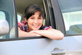 Young woman leaning out of the window of a car — Stock Photo