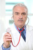 Doctor holding up the chestpiece of his stethoscope — Stock Photo