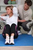 Donna fare sit-up, aiutato da allenatore di fitness — Foto Stock