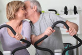 Man and woman on cross trainers kissing — Stock Photo