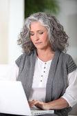 Vrouw die op haar laptop werkt — Stockfoto