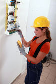 Female electrician with a fuse box — Stock Photo
