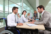Man in wheelchair working in an office — Stock Photo