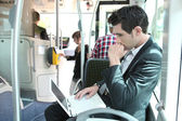 Man using laptop computer on a tram — Stock Photo