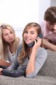 Three teenagers making a telephone call — Stock Photo
