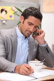 Homme d'affaires travaillant à la table du petit déjeuner — Photo