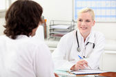 Smiling female doctor talking to a male patient — Stock Photo