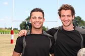 Two rugby players posing with ball in front of goal — Stock Photo
