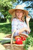 Mulher com um chapéu de palha e cesta de legumes. — Foto Stock