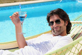 Man relaxing by the pool — Stock Photo
