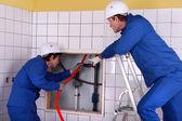 在公用卫生间中工作的两个水管工 — 图库照片