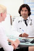 Blond woman in doctors appointment — Stock Photo