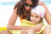 Mother drying daughter with towel at the beach — Stock Photo