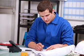 Manual worker in office ordering parts — Stock Photo