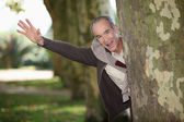 Man jumping out from behind tree — Stock Photo
