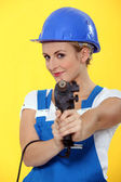 Pretty young woman using drill like a gun — Stock Photo