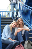 Two girlfriends sitting on the stairs at school — Stock fotografie