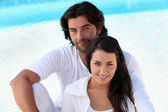 Loving young couple sitting by a pool — Stock Photo