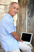 Man using his laptop outside — Stock Photo