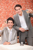 Young men in suits drinking in a wine bar — Stock Photo