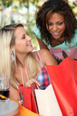 Excited girls watching their shopping bags — Stockfoto