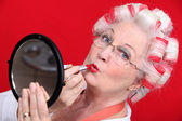 Senior woman with curlers in her hair putting lipstick — Stock Photo