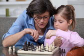 A mother teaching her daughter how to play chess. — Stock Photo