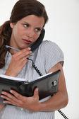 Secretary talking on the phone and looking at her agenda — Stockfoto