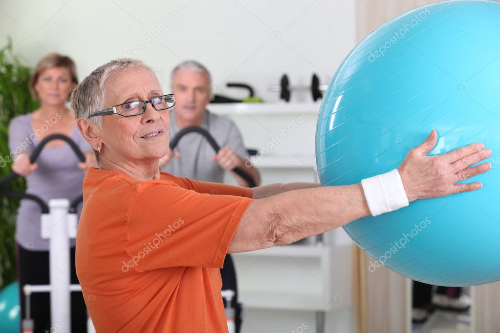 Senior woman lifting fitness balloon — Stock Photo #7373643