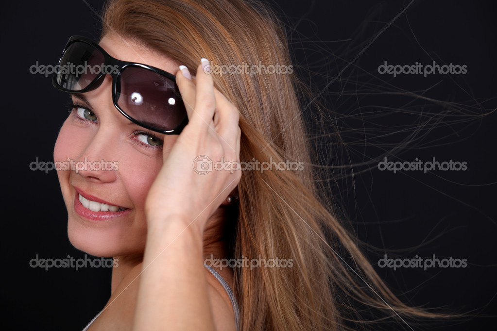 Woman wearing sunglasses on a breezy day — Stock Photo #7378502