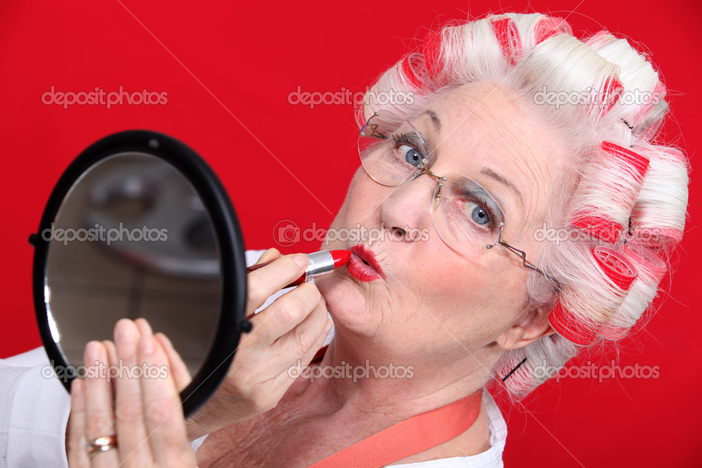 Senior woman with curlers in her hair putting lipstick — Stock Photo #7378560