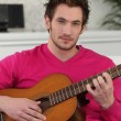 Royalty-Free Stock Photo: Young man playing a guitar
