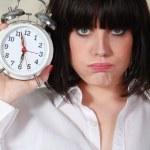 Grumpy woman holding an alarm clock — Stock Photo #7389094