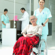 Nurse pushing older womin wheelchair — Stock fotografie #7389288