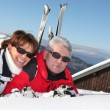 Mature couple lying in the snow outside their ski cabin — Stock Photo