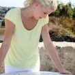 Blond woman looking at old stone map - Stock Photo
