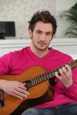 Giovane uomo che suona una chitarra — Foto Stock