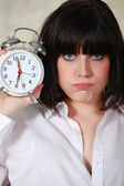 Grumpy woman holding an alarm clock — Stock Photo